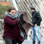 epa04069106 A woman struggles with her umbrella as she fights against the strong winds in San Sebastian, Spain, 11 February 2014. According to weather reports, the winds striking the north of the country have reached speeds up to 120 km/h.  EPA/LUIS TEJIDO