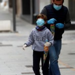 A man and a child wear protective face masks as they walk along the empty La Bola street, after restrictions were partially lifted for children for the first time in six weeks, during the coronavirus disease (COVID-19) outbreak in Ronda, Spain, April 26, 2020. REUTERS/Jon Nazca